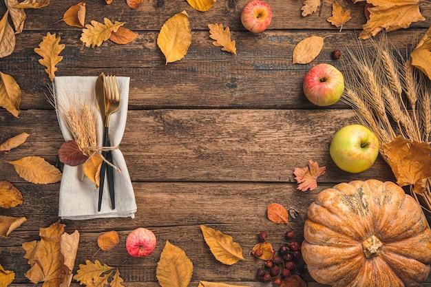 カトラリーの紅葉と木製の背景にカボチャとコンセプトのお祝いの秋の背景...