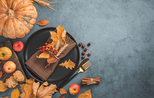 Festive autumn background with cutlery leaves and pumpkin on a dark background
