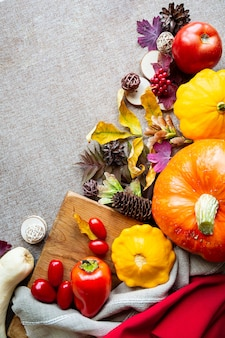 Festive autumn composition from pumpkins, leaves, tomato and squash on the beige background. concept of thanksgiving day or halloween