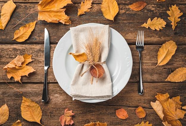 Праздничный осенний кулинарный фон с тарелкой, салфеткой и столовыми приборами