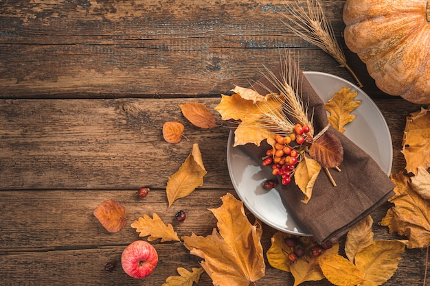 Festive autumn culinary background with a plate cutlery pumpkin and autumn leaves on a wooden backgr...