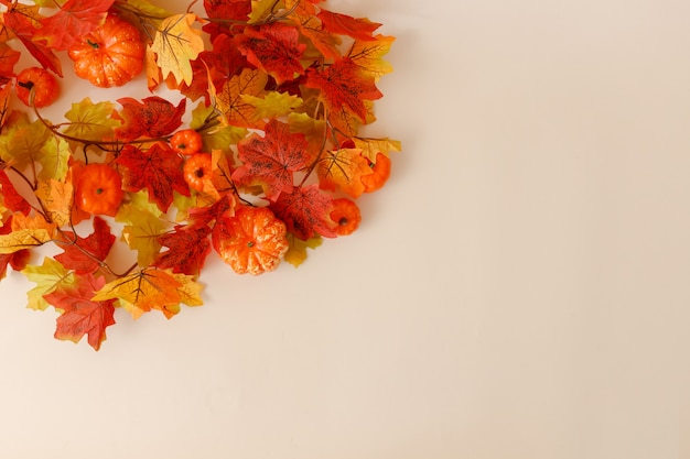 ベージュの背景にカボチャと葉でお祝いの秋の装飾