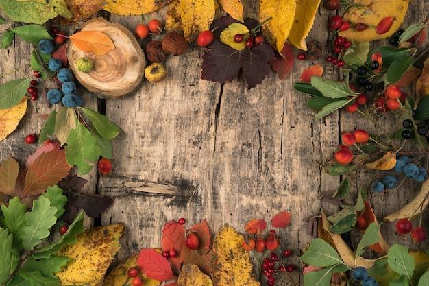 果実と自然な木製のテーブルの上の葉のお祝い秋モックアップ。