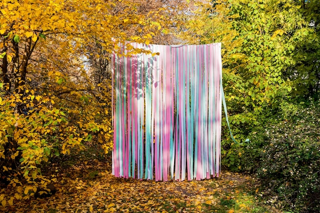 Festive autumn photo zone on the streets of multicolored ribbons, free space for inscriptions. holiday concept