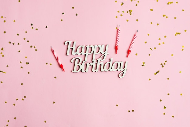 Festive backdrop from bright stars decoration, candles for cake and text happy birthday on a pink background.
