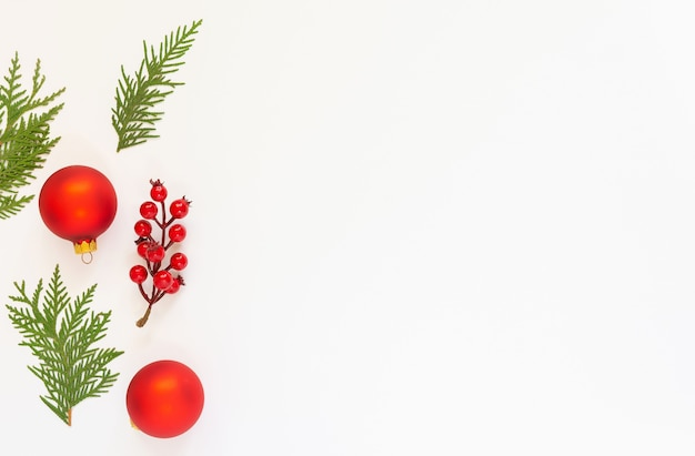 Festive background, branch of hawthorn and christmas tree balls with fir twigs on a white background, flat lay, top view, copy space