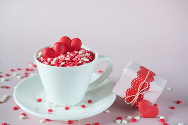 Festive background.  coffee cup, full of multicolor sweet sprinkles sugar candy hearts and packing valentine's  day gifts.  love and valentine's day concept.