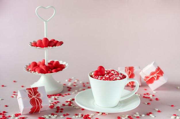 Праздничный фон. кофейная чашка, белый двухуровневый поднос, полный многоцветной сладости, брызгает сахарной конфетой сердца и упаковывает подарки дня валентинки любовь и концепция дня валентинки.