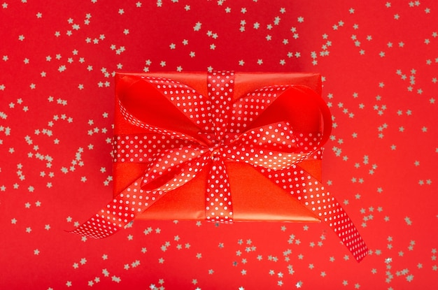 お祝いの背景、リボンとギフト ボックス、キラキラの銀の星と赤の背景に弓、フラット レイアウト、トップ ビュー