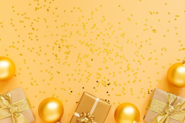 お祝いの背景、ギフト ボックス、クリスマス ボールの背景にキラキラの金の星、フラット レイアウト、トップ ビュー、コピー スペース