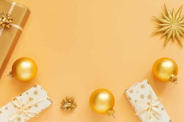 お祝いの背景、金色の背景にきらめく金の星とギフト ボックス、クリスマス ボール、フラット レイアウト、平面図、コピー スペース