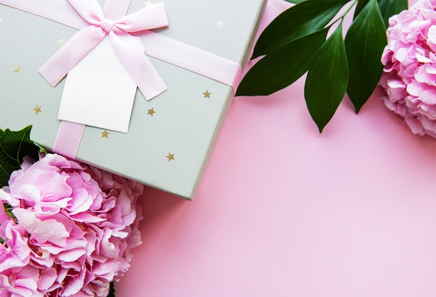 Festive background for a greeting card with a  silver gift box with a bow and flowers of  hydrangea in pink colors
