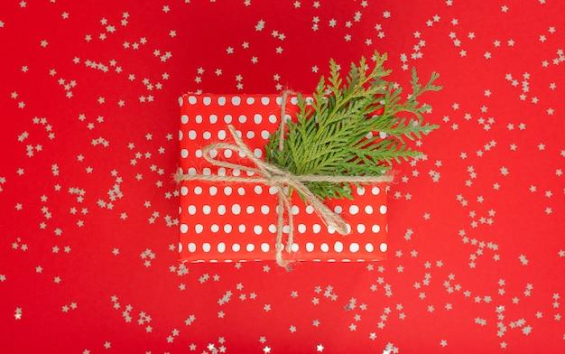 축제 배경, 리본과 활이 있는 물방울 무늬의 빨간색 선물 상자, 반짝이는 은색 별이 있는 빨간색 배경에 있는 thuja 잔가지, 평평한 평지, 위쪽 전망