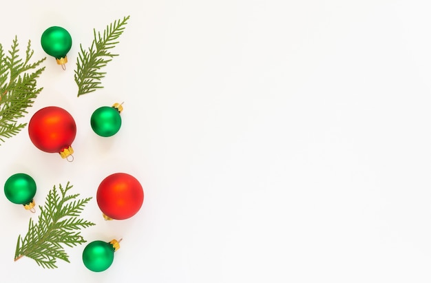 Festive background, red and green christmas tree balls with fir twigs on a white background, flat lay, top view, copy space