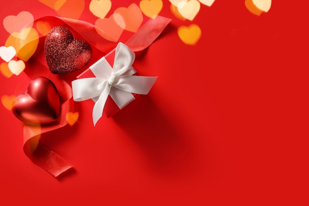 Festive background for valentine's day. two hearts, silk ribbon and gift box on a red background with copy space.