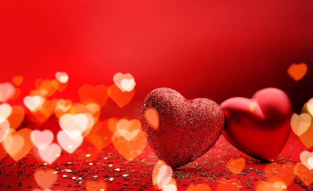 Festive background for valentine's day with copy space. heart shaped two hearts on a red background with sparkles and bokeh.