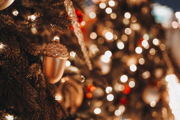 美しい黄金のボケ味のお祝いの背景は、クリスマスのおもちゃのどんぐりモミの枝を照らします