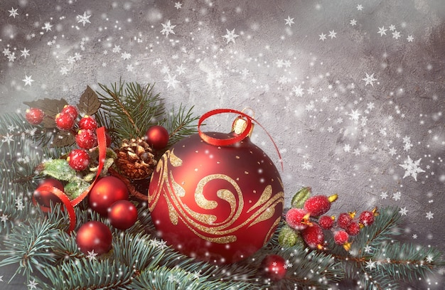 Festive background with christmas tree twigs decorated with red baubles and fir twigs