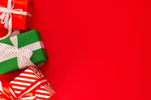 색색의 선물이 있는 축제 배경, 빨간색 배경에 리본과 활이 있는 선물 상자, 평평한 평지, 위쪽 보기, 텍스트를 위한 빈 공간