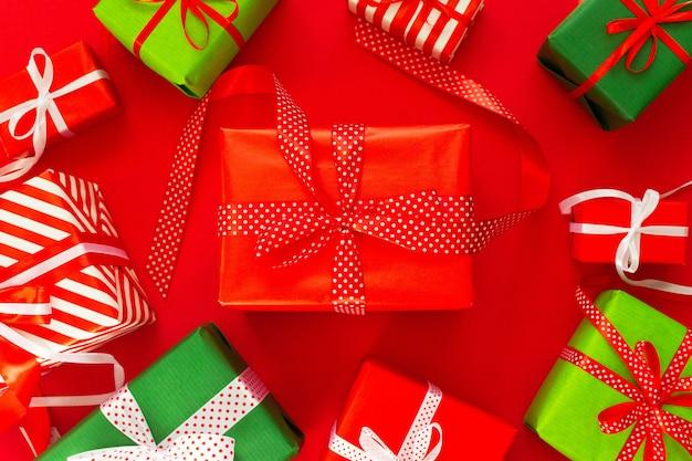 색색의 선물이 있는 축제 배경, 빨간색 배경에 리본과 활이 있는 선물 상자, 평평한 평지, 위쪽 전망