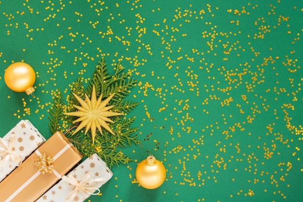 장식, 밝은 골드 스타와 선물 상자와 녹색 배경에 크리스마스 공 축제 배경
