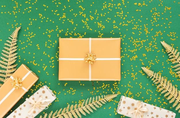 装飾、明るい光沢のある金色のシダの葉、キラキラの金の星、フラットレイ、上面図、コピースペースと緑の背景にギフトボックスとお祝いの背景