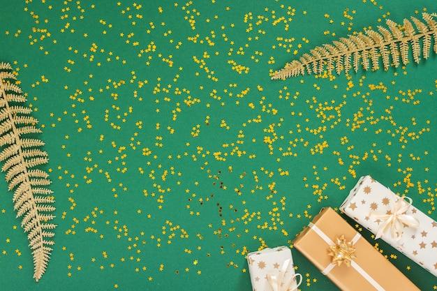 華やかな背景に装飾、明るい光沢のある金色のシダの葉、緑の背景にギフトボックス、きらめく金色の星、フラットレイ、トップビュー、コピースペース