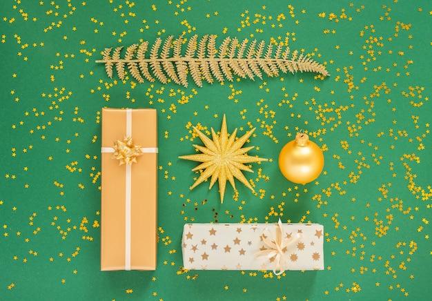 お祝いの背景に装飾、明るい光沢のある金色のシダの葉、緑の背景にクリスマス ボールが付いたギフト ボックス、きらめく金の星、フラット レイアウト、トップ ビュー、コピー スペース