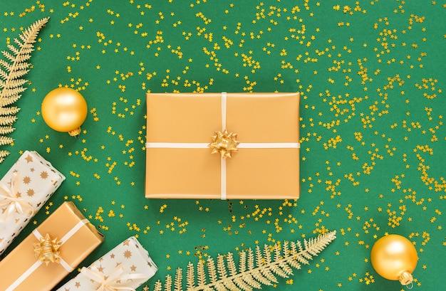 お祝いの背景に装飾、明るい光沢のある金色のシダの葉、緑の背景にクリスマス ボール付きのギフト ボックス、きらめく金の星、フラット レイアウト、トップ ビュー、コピー スペース