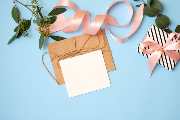 Festive background with envelope, greeting card and flowers.