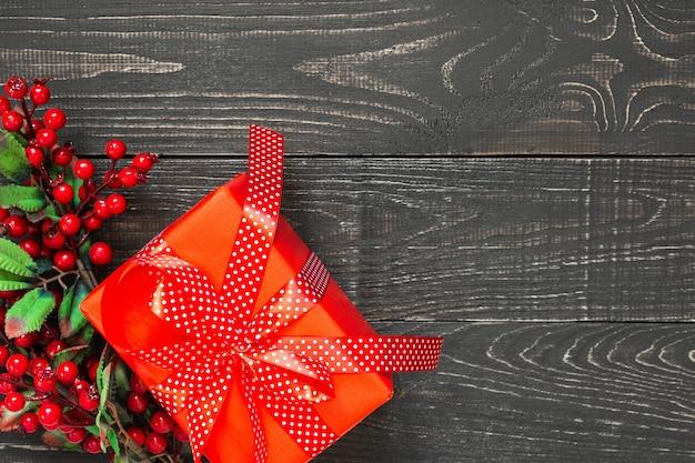 선물과 호손이 있는 축제 배경, 물방울 무늬 리본이 있는 빨간색 선물 상자, 갈색 천연 나무 배경에 활, 평평한 평지, 위쪽 전망