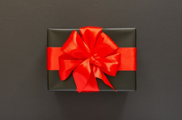 Festive background with gift, black gift box with red ribbon and bow on black background, black friday concept, flat lay, top view