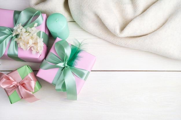 선물 상자, 촛불, 흰색 나무 바탕에 스웨터와 축제 배경.