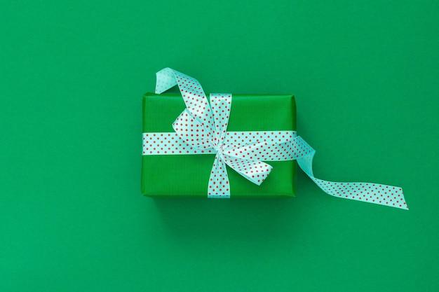 선물이 있는 축제 배경, 물방울 무늬 리본이 있는 선물 상자, 녹색 배경에 활, 평평한 평지, 위쪽
