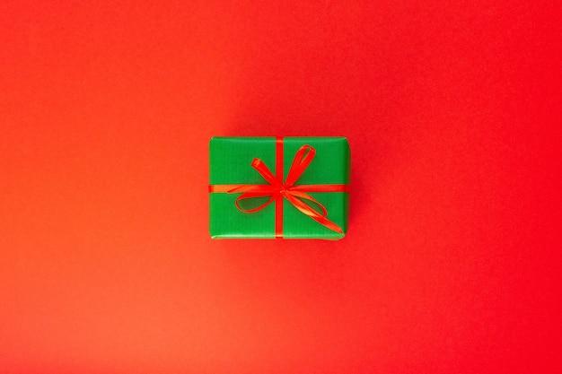 선물이 있는 축제 배경, 리본이 달린 녹색 선물 상자와 빨간색 배경에 활, 평평한 평지, 위쪽 전망