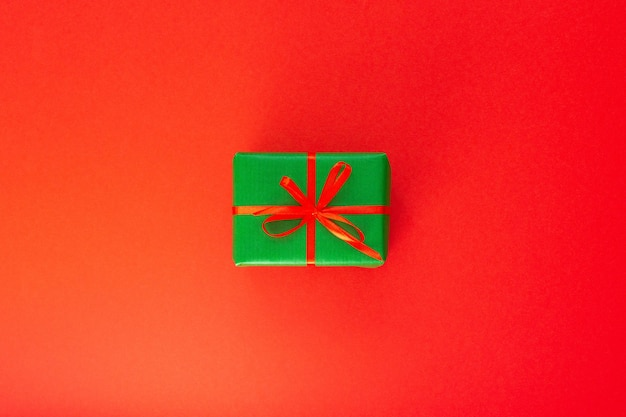 Festive background with gift, green gift box with ribbon and bow on red background, flat lay, top view