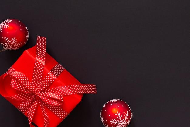 선물이 있는 축제 배경, 물방울 무늬 리본이 있는 빨간색 선물 상자, 검은 배경에 크리스마스 공, 검은 금요일 개념, 평평한 평지, 위쪽 전망
