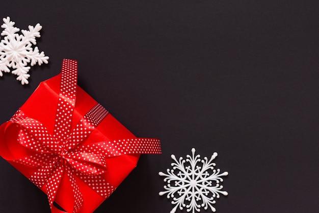 선물이 있는 축제 배경, 물방울 무늬 리본이 있는 빨간색 선물 상자, 검은 배경에 활과 눈송이, 검은 금요일 개념, 평평한 평지, 위쪽 전망