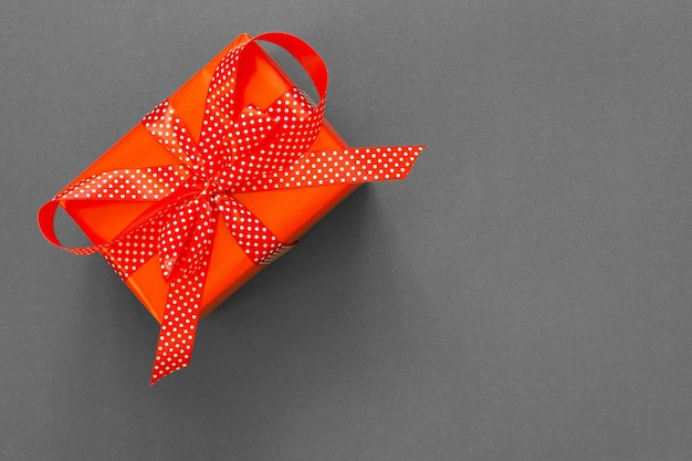 선물 축제 배경, 물방울 무늬 리본이 달린 빨간색 선물 상자와 회색 배경, 검은 금요일 개념, 평면 평신도, 평면도에 활