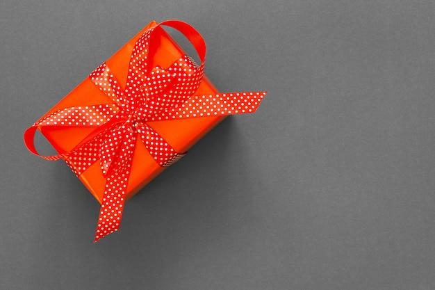 Праздничный фон с подарком, красная подарочная коробка с лентой в горошек и бантом на сером фоне, концепция черной пятницы, плоская планировка, вид сверху