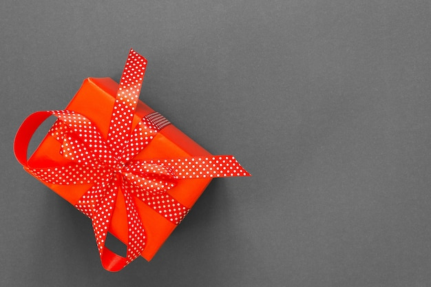 선물이 있는 축제 배경, 물방울 무늬 리본이 있는 빨간색 선물 상자, 회색 배경에 활, 검은 금요일 개념, 평평한 평지, 위쪽 전망