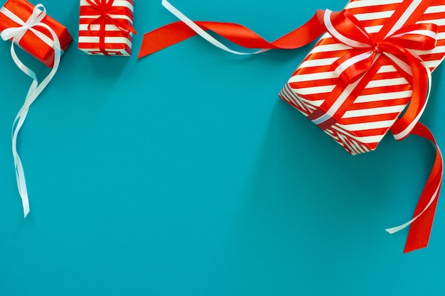 Праздничный фон с подарками, подарочная коробка с лентой и бантом на синем бирюзовом фоне, плоская планировка, вид сверху