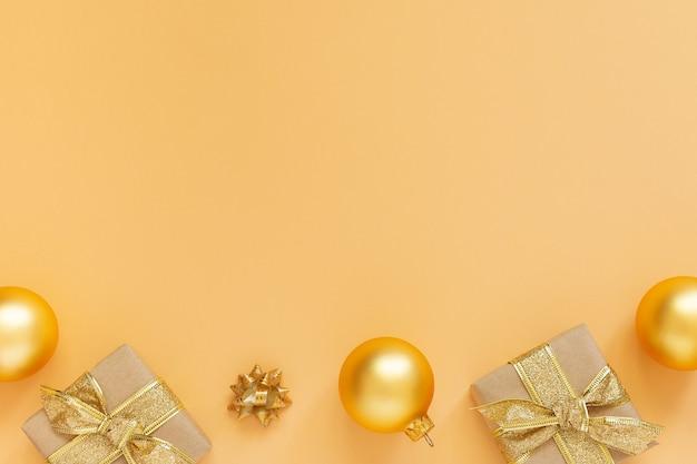 ゴールドの装飾が施されたお祭りの背景、ゴールドの背景にギフト ボックスとクリスマス ボール、フラット レイアウト、トップ ビュー、コピー スペース