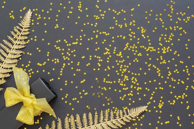 Праздничный фон с золотыми украшениями, блестящими золотыми листьями папоротника и подарочной коробкой на черном фоне с блестящими золотыми звездами, плоская планировка, вид сверху, копия пространства
