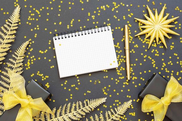 금색 장식, 반짝이는 황금색 고사리 잎, 선물 상자가 반짝이는 금색 별, 열린 나선형 메모장 및 펜, 평평한 평지, 위쪽 전망이 있는 축제 배경
