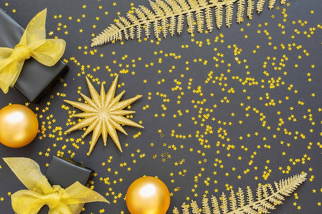 금 장식, 반짝이는 황금 고사리 잎, 크리스마스 공이 있는 선물 상자가 반짝이는 금색 별, 평평한 평지, 위쪽 전망, 복사 공간이 있는 축제 배경