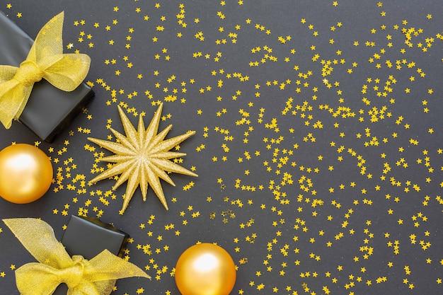 金の装飾が施されたお祭りの背景、光沢のある金色の星とギフト ボックス、クリスマス ボールと黒の背景にきらめき金の星、フラット レイアウト、平面図、コピー スペース