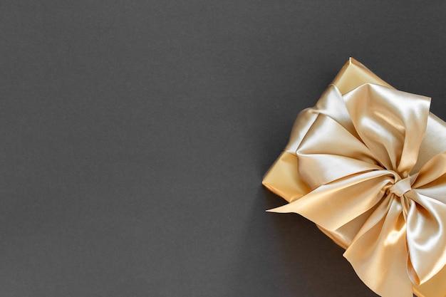 금 선물이 있는 축제 배경, 금 리본이 있는 상자와 검은색 배경에 활, 평평한 평지, 위쪽 전망, 복사 공간