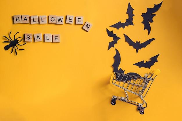 거꾸로 된 쇼핑 카트에 박쥐와 종이 거미가 있는 할로윈 판매 글자가 있는 축제 배경. 파티나 판매를 위해 평평하게 비웃습니다. 평면도. 복사 공간