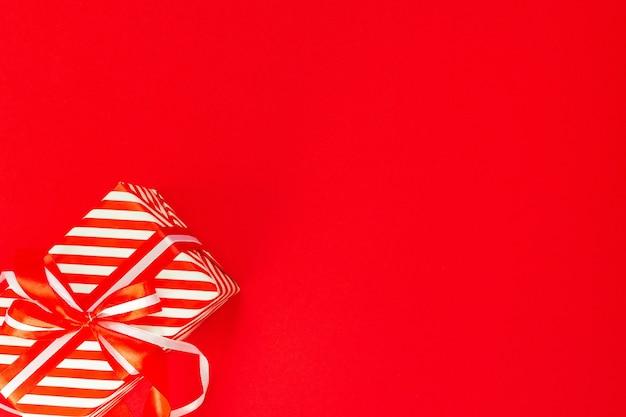 빨간색과 흰색 줄무늬 선물이 있는 축제 배경, 빨간색 배경에 리본과 활이 있는 선물 상자, 평평한 평지, 위쪽 전망